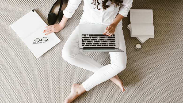 woman sitting on the floor doing work on her computer