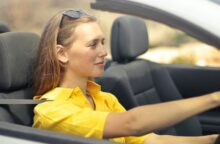 A woman in a bright yellow dress drives a silver car.